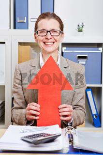 Businessfrau hält roten Pfeil nach oben