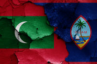 flags of Maldives and Guam painted on cracked wall