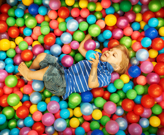 Happy child playing with colorful plastic balls