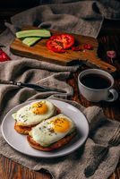 Bruschettas with vegetables and fried eggs with cup of coffee