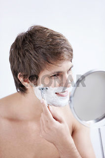Young man shaving at the mirror on a white background