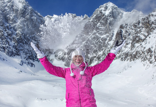 Young woman in pink ski jacket, gloves and winter hat, smiling, throwing snow in the air, sun shining on mountain behind her. Skalnate Pleso skiing resort, Slovakia.