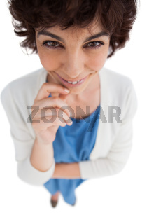 Overhead of smiling woman with hand touching her chin