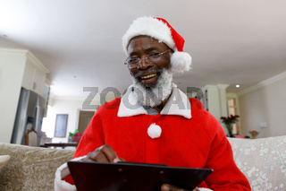 Portrait of senior african american man wearing a costume of santa claus and writing on clipboard