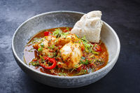 Modern style traditional Spanish seafood zarzuela de pescado with fish served and bread in red sauce as close-up in a design bowl