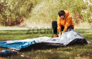 man setting up tent outdoors