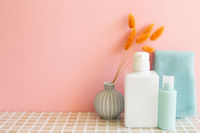 Bathroom bottles, shower towel, vase of plant on mosaic tile table. pink wall background. Skin care and spa concept. Home interior