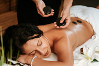 Beautiful young woman in the massage salon with brown curly hair and healthy skin. Masseur and patient concept.