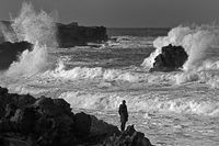 A woman stands on the black lava coast and looks at the huge sea surf, Skardsvik, Iceland