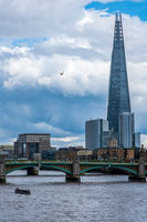 The Shard skyscraper landmark building dominating the skyline behind the Southwark Bridge.