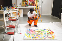African american male painter at work taking picture of artwork with smartphone in art studio
