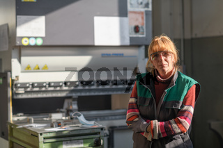portrait of a woman standing in front of a CNC machine in goggles and working in a modern metal production and processing factory