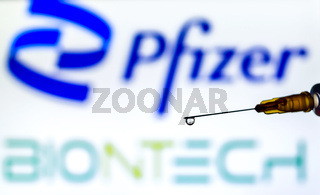 Syringe with liquid back lit by the logos of Pfizer and Biontech, developers of Covid19 vaccine