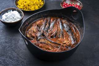 Modern style slow cooked Persian lamb eggplant stew khoresh bademjan served with rice and yoghurt as close-up in a design pot