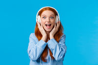 Excited and amused attractive caucasian redhead woman in pyjama, screaming from fascination and amazement hear new song, wearing headphones enjoy music, standing blue background