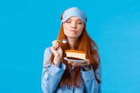 Delicious food, lifestyle and people concept. Delighted and happy cute redhead female in pyjama and sleep mask, close eyes and licking lips as eating tasty cake, holding spoon smiling