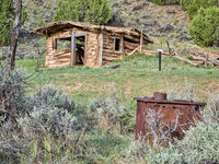 small, old, log cabin sits on a hillside