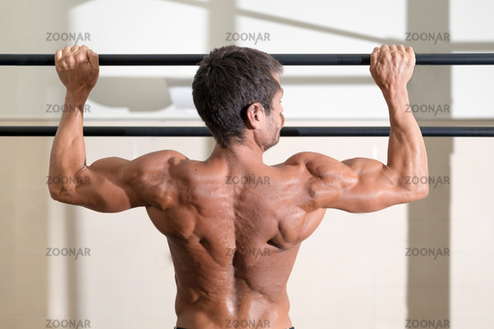 Athlete doing pull-ups at the gym. Handsome man doing functional training.