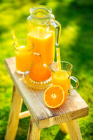 Two glasses of tasty freshly squeezed orange juice on garden stool on green lawn