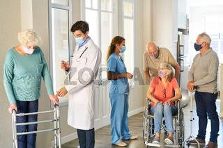 Senioren und Klinikpersonal mit Maske im Pflegeheim
