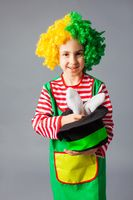 The little girl in a clown's costume demonstrates trick with a bunny