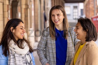 Multiracial group of girls walking in the city. Urban background with busy road and sidewalk, friendship and lifestyle concepts.Group consists of indian, asian and caucasian girls