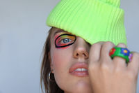 Portrait of young woman with creative make-up, wears bright knitted beanie hat.