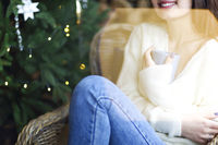 Cute smiling woman with aromatic hot drink while resting on brightly illuminated background
