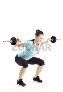 Sportlerin macht Kniebeugen mit Langhantelstange
