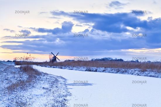 Dutch windmill in winter at sunrise