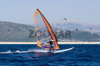 Windsurfing along the coast in the middle of the kite