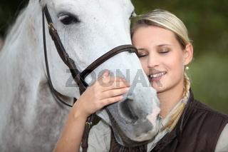 Blond woman petting horse