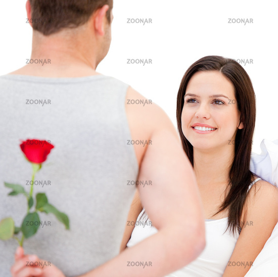 Handsome man hidding a rose against a white background