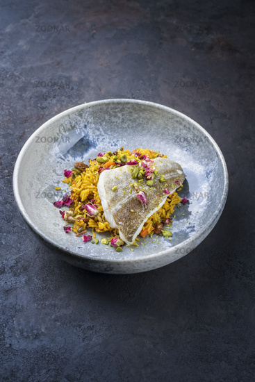 Modern style traditional sauteed skrei cod fish filet with skin in a bed of Persian jeweled saffron rice pilaw served in ceramic design bowl with copy space