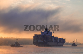 Schlepper bugsieren Frachter im Sonnenaufgang