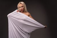 Sexy woman wrapped in white cloth in studio