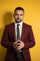 Successful businessman. Portrait of handsome man in burgundy color suit looking at camera with hands folded isolated on yellow background. Vertical photo