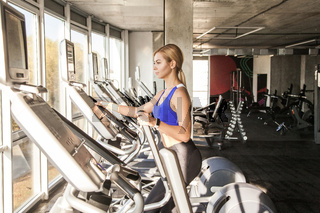 Woman in fitness club or gym, ride on orbitrack, exercise bike