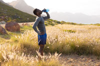 Portrait of fit african american man in sportswear resting drinking water in tall grass