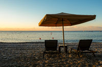 Beach umbrellas and relaxing chairs at sea at sunrise. Empty beach Pissouri Cyprus