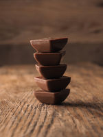 Stacked chocolated pieces on a rustic wooden table