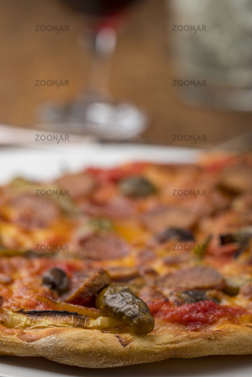 Close up of pizza with wine on wood