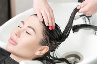 Hairstylist's hands wash long hair of brunette woman with shampoo in special sink for shampooing
