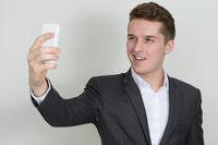 Portrait of happy young handsome businessman in suit taking selfie