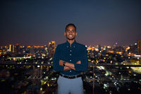 African businessman outdoors at rooftop smiling with arms crossed