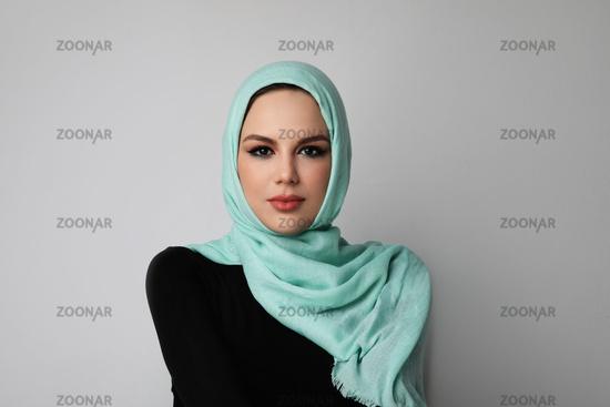 Portrait of happy muslim woman wearing green hijab. Light background.