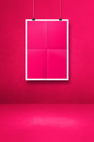 pink folded poster hanging on a clean wall with clips
