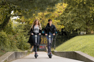 Trendy fashinable teenagers riding public rental electric scooters in urban city park. New eco-friendly modern public city transport in Ljubljana, Slovenia
