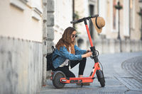 Electro-mobility. Traveler unlocking an e-scooter on the street. Traveler exploring old town on environmentally friendly electric scooter
