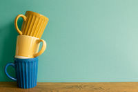 Stack of mug cup on wooden table. mint wall background. copy space